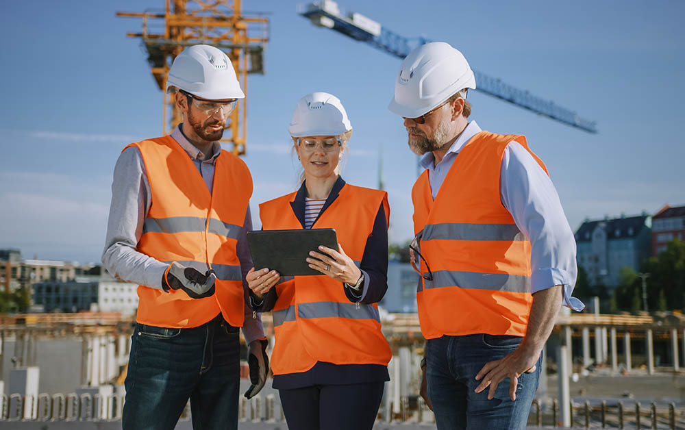 People look at a tablet on a construction site.
