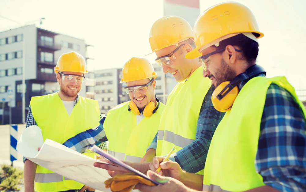 Construction workers smiling over plans
