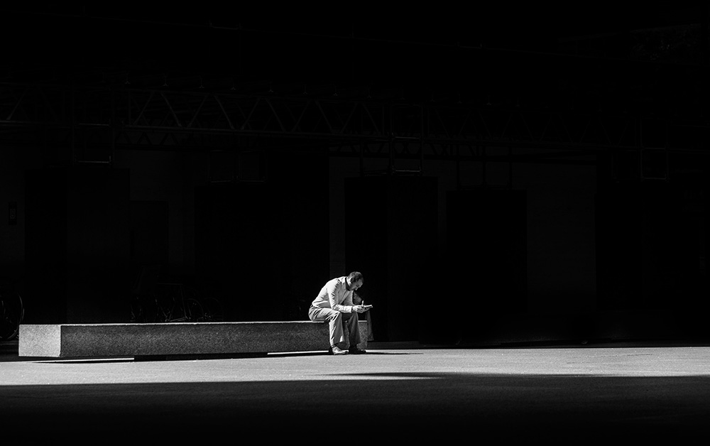 Man sits alone in stark light