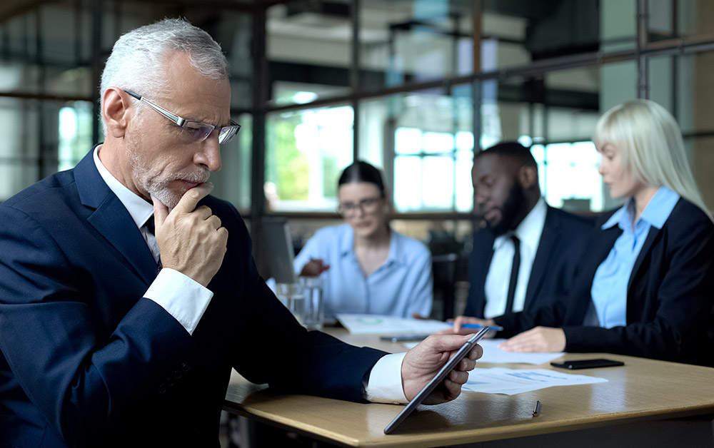 A businessman looks pensively at a tablet.